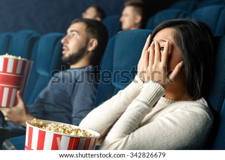 Horror movies are for brave ones. Closeup shot of a scared girl closing her eyes with her hands watching scary movie in the cinema