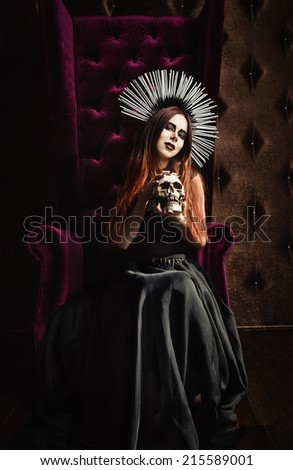 Horror photo: a beautiful gothic girl in black dress holds the skull - stock photo