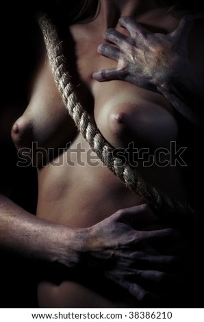 Horror photo of the woman breast embraced by the dead hands - stock photo