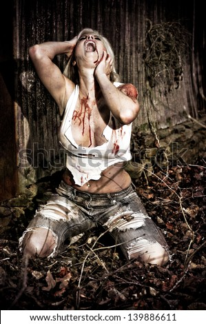 Horror scene of a bloody woman screaming in the woods by an old cabin - stock photo