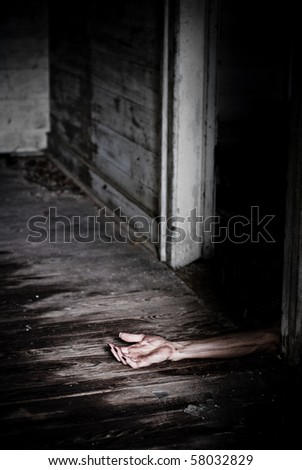 Horror scene of a dead like arm on the floor hanging out of a doorway. - stock photo