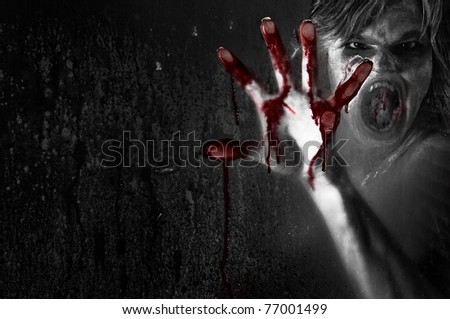Horror Scene of a Possessed Woman with Bloody Hand against Wet Glass space for text to the left - stock photo