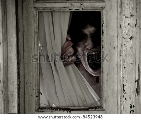Horror Scene of a Scary Woman peeking out of a small window focus is on mouth - stock photo