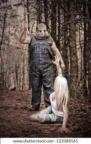 Horror scene of a woman crawling in the woods away from a hooded man with an Axe. - stock photo