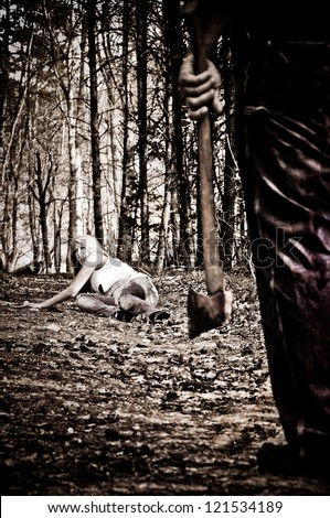 Horror scene of a woman crawling in the woods away from a man with an Axe. - stock photo