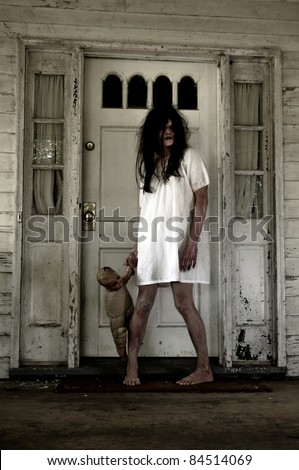 Horror Scene of a Woman Possessed holding a doll at front door of an old house - stock photo