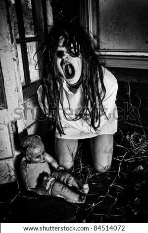 Horror Scene of a Woman Possessed Screaming wearing a straight jacket with a doll - stock photo