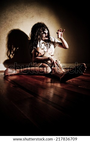 Horror Scene of a Woman Possessed Sitting with a doll  - stock photo