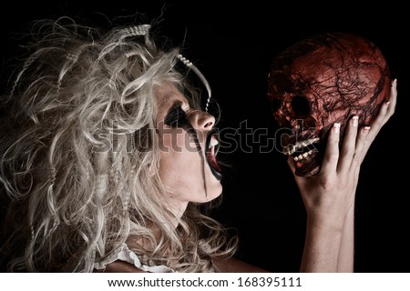 Horror Scene of a Woman Possessed yelling at a skull - stock photo