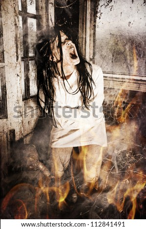 Horror Scene of a Woman Screaming Wearing a Straight Jacket in a Room Full of Fire and Smoke - stock photo