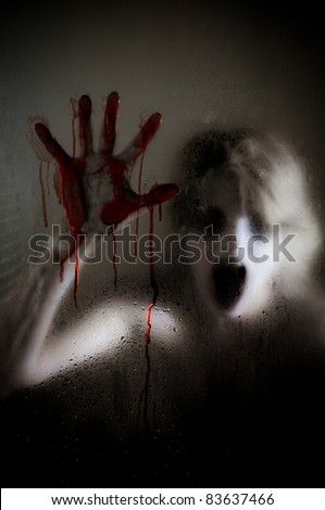 Horror Scene of a Woman with Bloody Hand against Wet Shower Glass Focus is on Glass - stock photo