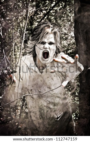 Horror Scene of a Zombie in the woods - stock photo