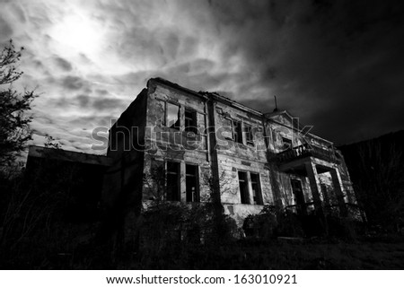 Horror scene of the old grunge building at night over cloudy sky and the moon behind  - stock photo