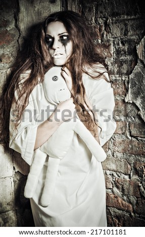 Horror scene: the strange crazy girl with moppet doll in hands - stock photo