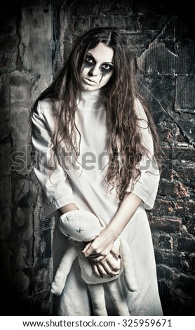 Horror scene: the strange mysterious girl with moppet doll in hands - stock photo