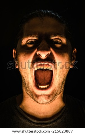 Horror scene with screaming scary human face with a harsh light on a black background - Halloween concept with young man with open mouth and teeth - stock photo