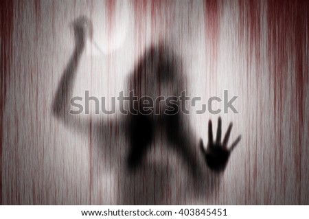 Horror shadow woman figure with a  scissors behind the matte glass blood stain.  Blurry abstraction concept - stock photo