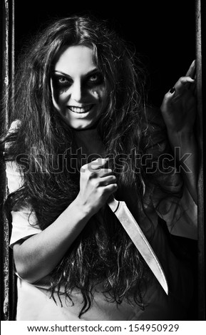 Horror style shot: a crazy evil girl with knife in hands. Black and white - stock photo
