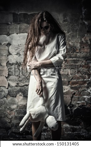 Horror style shot: a scary monster girl with moppet doll in hands - stock photo