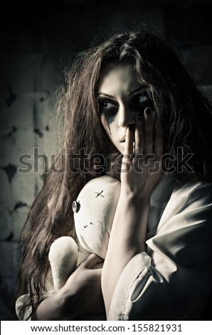 Horror style shot: a strange sad girl with moppet doll in hands - stock photo