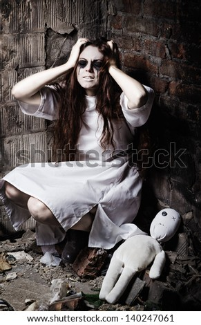 Horror style shot: the strange crazy girl and her moppet doll - stock photo