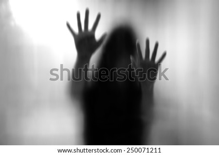 Horror woman behind the matte glass in black and white. Blurry hand and body figure abstraction. - stock photo