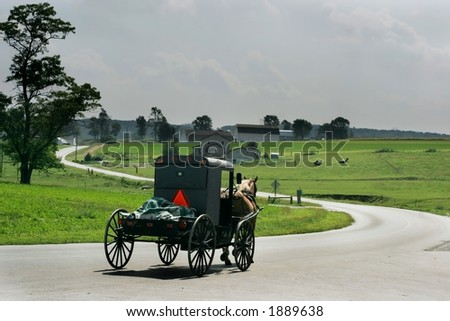 horse and carriage going down winding road - stock photo