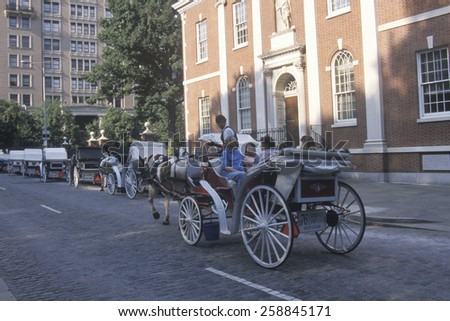Horse and carriage riding in historic district of old Philadelphia, PA, in front of Independence Hall, home of Declaration of Independence and US Constitution - stock photo