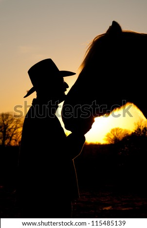 Horse and his cowboy silhouetted against a sunset, head to head - stock photo
