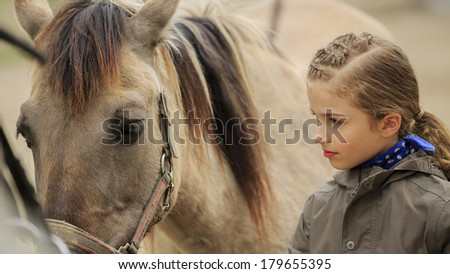Horse and lovely girl - young girl takes care of the horse - stock photo