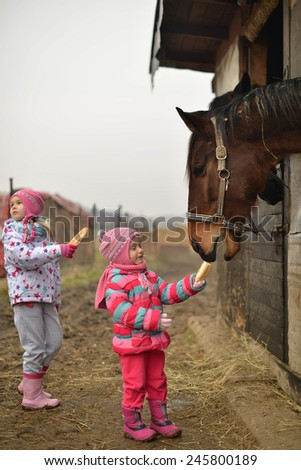 horse and two little girls - stock photo