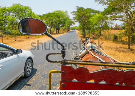 Horse carriage and car on rural road, Myanmar - stock photo