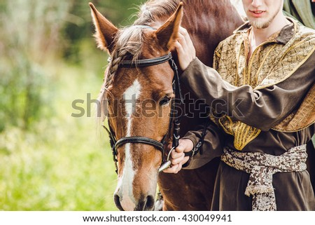 horse closeup. close up of a horse head with detail on the eye and on rider hand. a stallion horse being riding. - stock photo