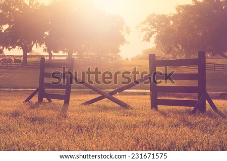 Horse cross rail jump obstacle hurdle in a field for practice training at sunset sunrise with vintage retro aged filter and sun flare - stock photo