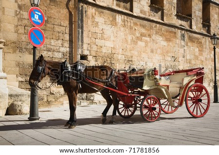Horse drawn carriage in parking lot, Mallorca, Spain - stock photo
