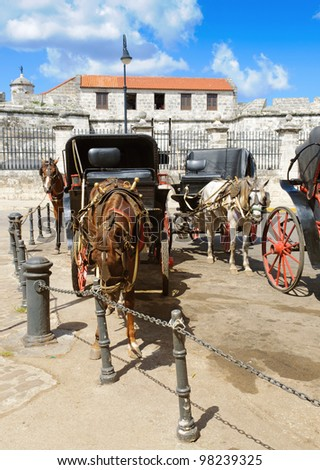 Horse drawn carriages parked in Plaza de Armas, Old Havana - stock photo
