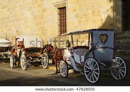 Horse drawn carriages waiting for tourists in historic Guadalajara, Jalisco, Mexico - stock photo