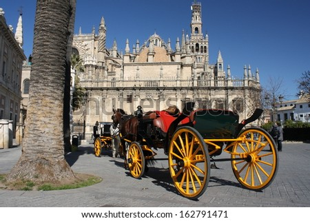 horse driven coach in front of cathedral in Seville - stock photo