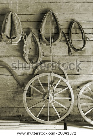 Horse harness and wheels on a wall. - stock photo