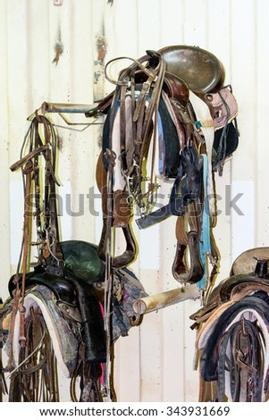 Horse harness suspended from a hook on the wall in the stable - stock photo