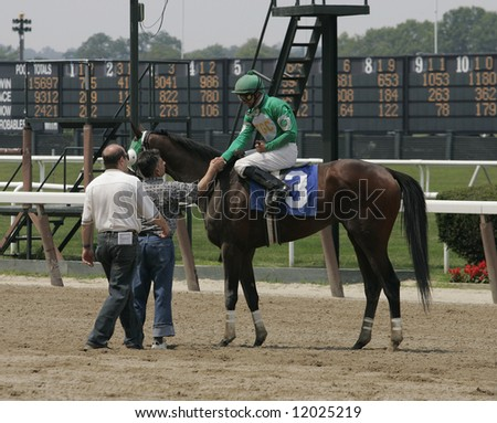 Horse Owner and Trainer Congratulate Jockey on Winning Horse - stock photo