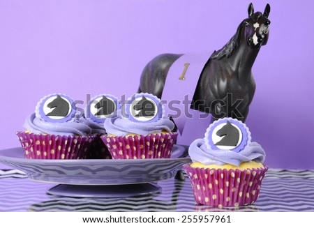 Horse racing carnival party luncheon cupcakes with horse decorations in purple, black and white chevron stripe theme . - stock photo