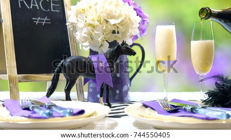 Horse racing Racing Day Luncheon fine dining table setting with small black fascinator hat, decorations and champagne, pouring two glasses of champagne.