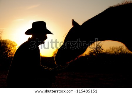 Horse reaching towards his trusted person, a man in cowboy hat, silhouetted against winter sunset - stock photo