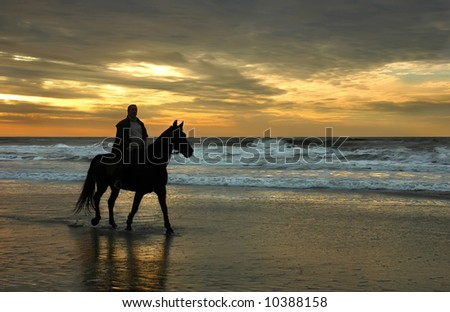Horse rider on North Sea beach silhouetted by setting sun. - stock photo