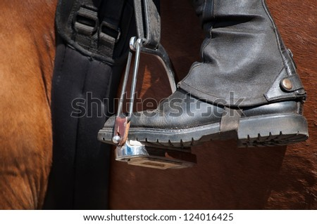 Horse rider's black riding boot in stirrup. Red horse. Horse racing.
