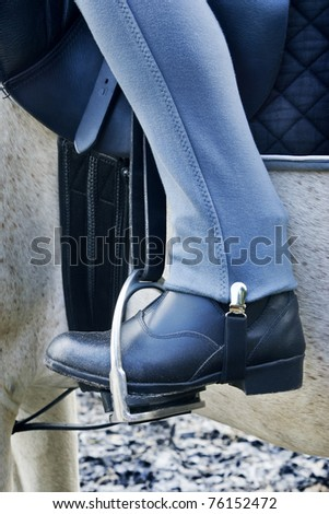 Horse rider's boot in stirrup - stock photo