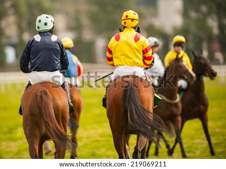 horse riders on the race track - stock photo