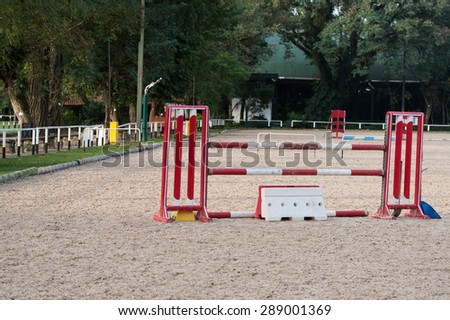 Horse riding club obstacles and sticks in sandy terrain - stock photo