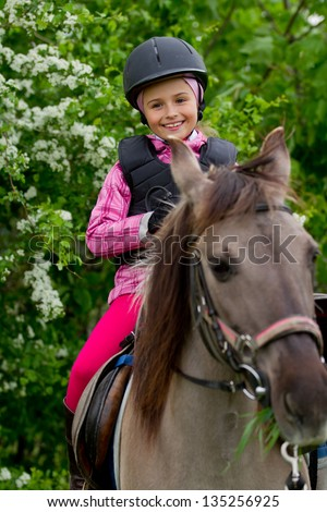 Horse riding - lovely equestrian is riding on a horse - stock photo